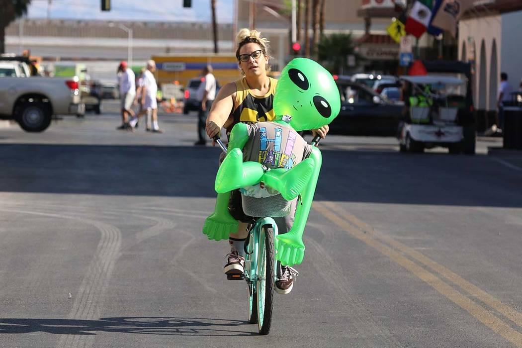 "Sasha Romandetti of Las Vegas rides her bike with ""Gilbert the Alien"" in downtown Las Vegas on ..."
