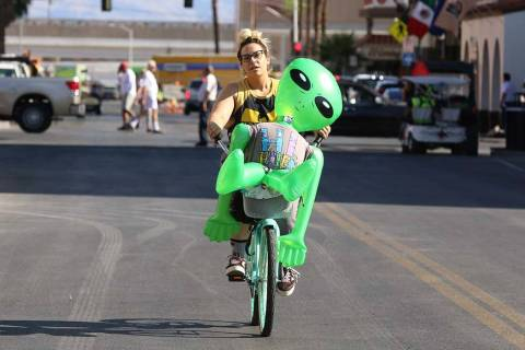 "Sasha Romandetti of Las Vegas rides her bike with ""Gilbert the Alien"" in downtown Las Vegas on ..."