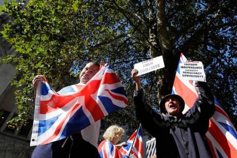 Demonstrators hold placards and flags outside the Supreme Court in London, Wednesday, Sept. 18, ...