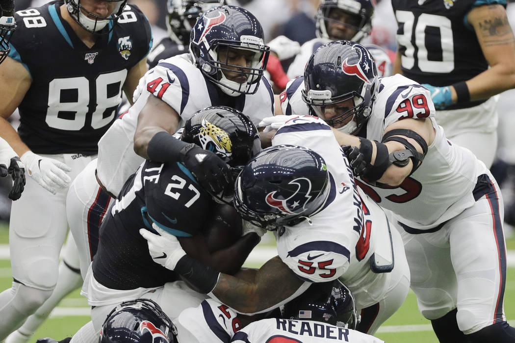 Jacksonville Jaguars running back Leonard Fournette (27) is stopped by Houston Texans inside li ...