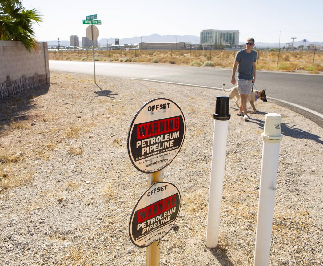 Trevor Schneider, walks his dog near the Petroleum Pipeline sign on Wednesday, Sept. 18, 2019, ...