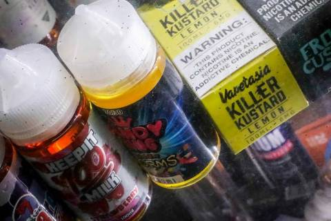 In this Sept. 16, 2019 file photo flavored vaping solutions are shown in a window display at a ...