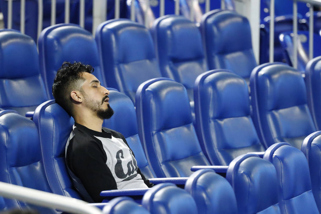 A spectator naps during the playing of the National Anthem before the start of a baseball game ...