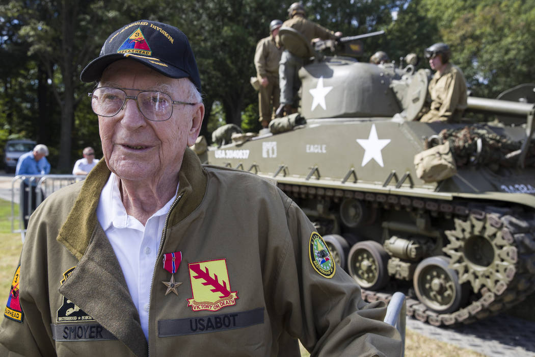 World War II veteran Clarence Smoyer, 96, poses for a picture in front of a Sherman tank after ...