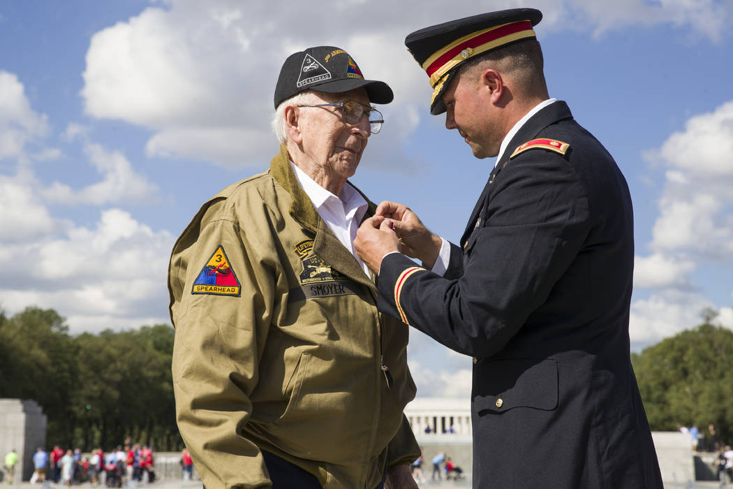 World War II veteran Clarence Smoyer, 96, receives the Bronze Star from U.S. Army Maj. Peter Se ...