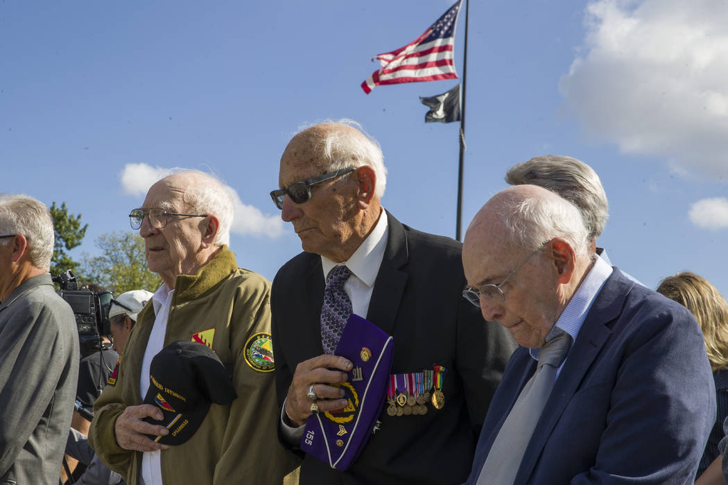 World War II veterans Clarence Smoyer, 96, left, Joseph Caserta and Buck Marsh bow their heads ...