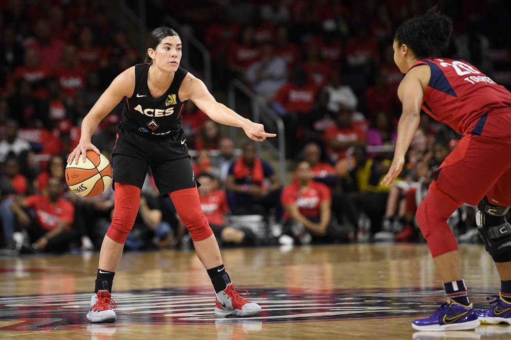 Las Vegas Aces guard Kelsey Plum, left, dribbles the ball against Washington Mystics guard Kris ...