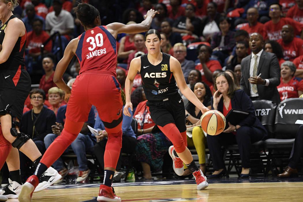 Las Vegas Aces guard Kelsey Plum, right, dribbles the ball against Washington Mystics forward L ...