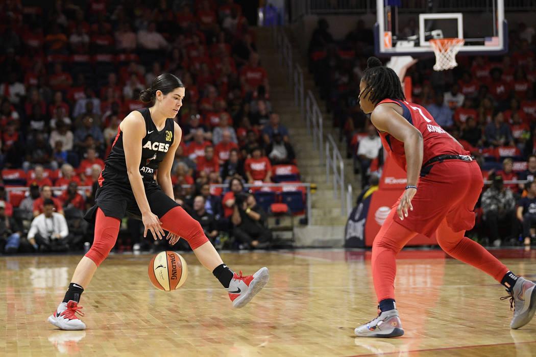 Las Vegas Aces guard Kelsey Plum, left, dribbles the ball against Washington Mystics guard Arie ...