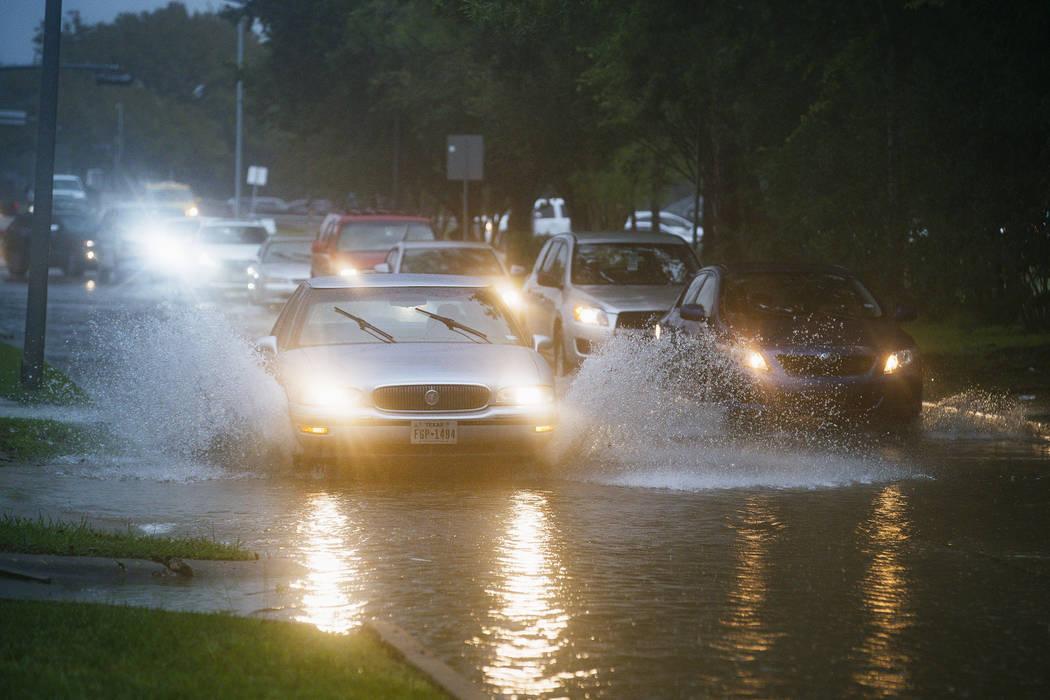 Vehicles splash through heavy water filling Chimney Rock, south of Brays Bayou in Houston, Tues ...