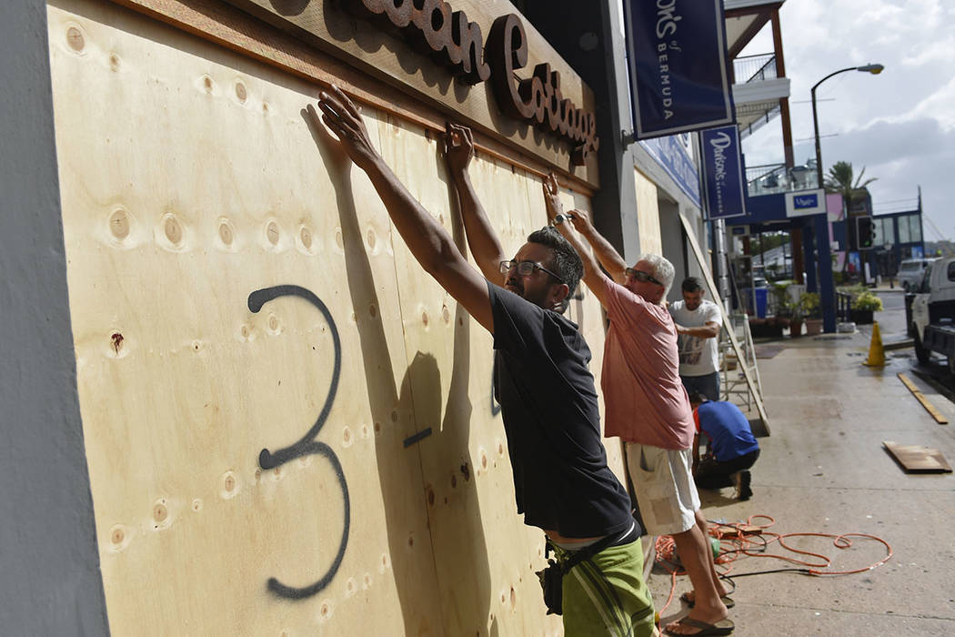 People board up an Urban Cottage store in preparation for Hurricane Humberto in Hamilton, Bermu ...
