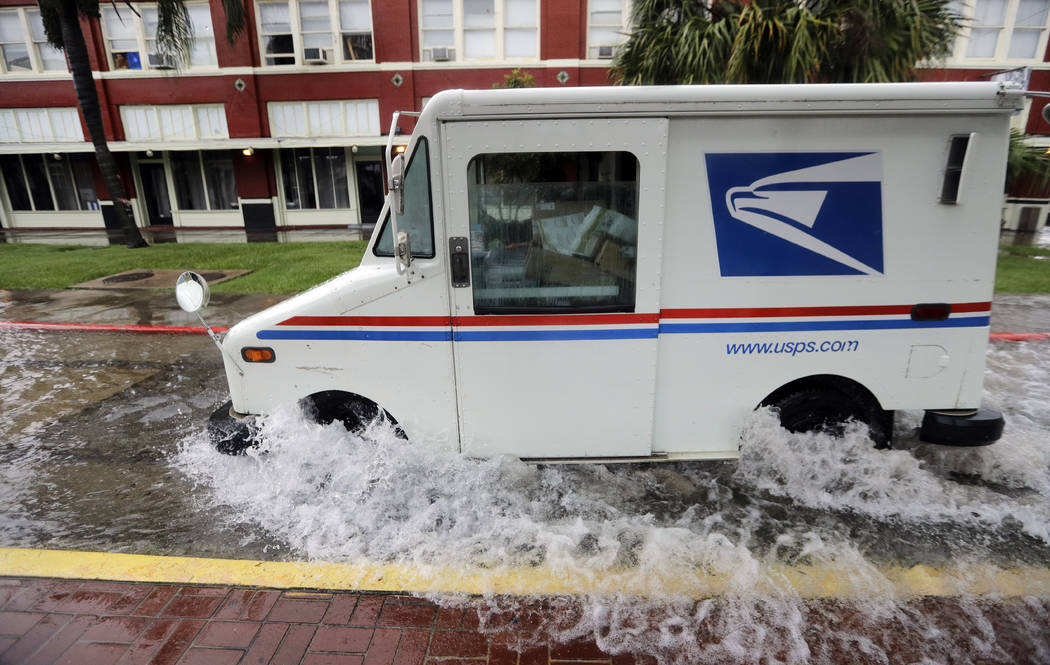 A postal truck drives through floodwaters from Tropical Depression Imelda, Wednesday, Sept. 18, ...