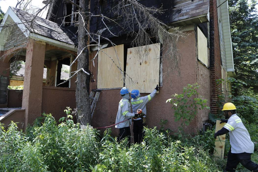 FILE - In this June 11, 2019 file photo, members of the Detroit's Board Up Brigade board up a v ...