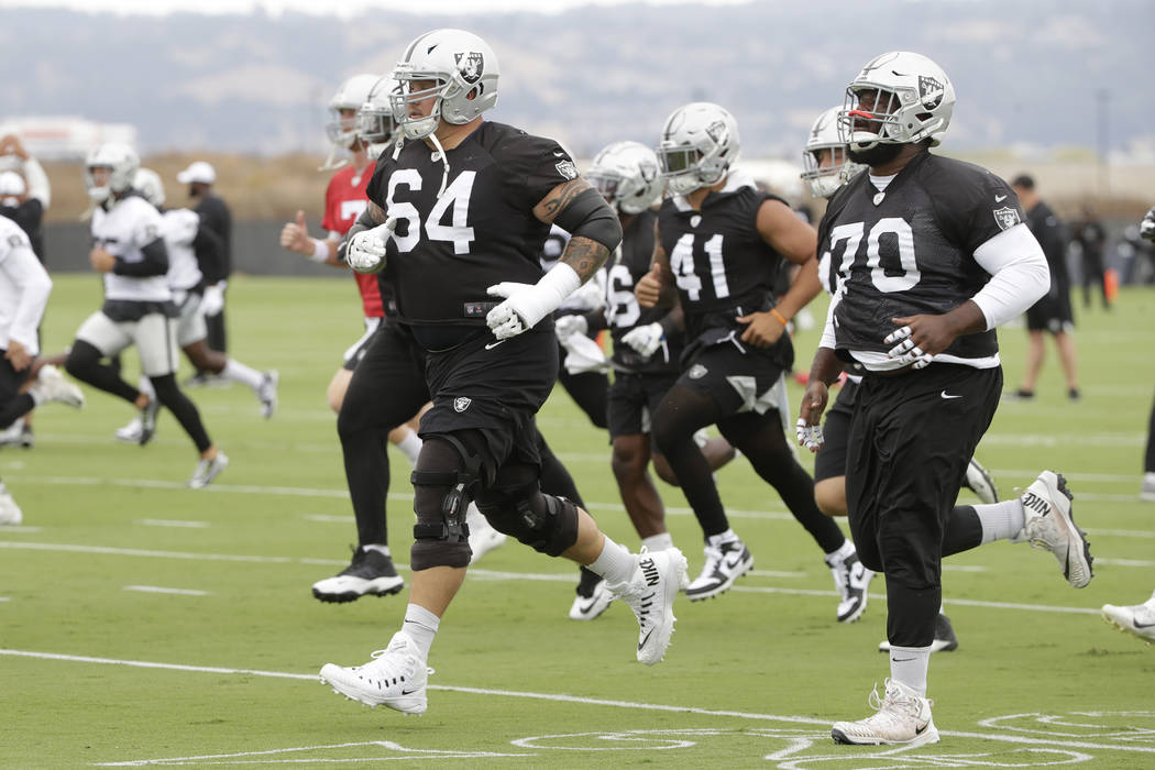 Oakland Raiders' Richie Incognito (64) jogs next to Jonathan Cooper (70) during NFL football pr ...
