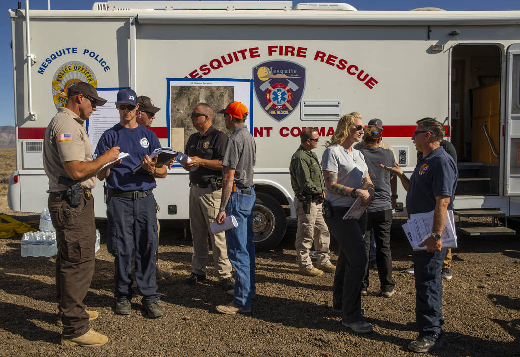 Emergency personnel confer while beginning to man the Incident Command Post in the Tikaboo Vall ...