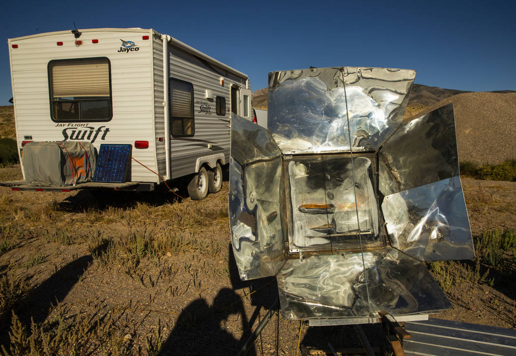 Ken Faulhaber of Las Vegas cooks dinner in a solar over while camped out with friends as the Al ...