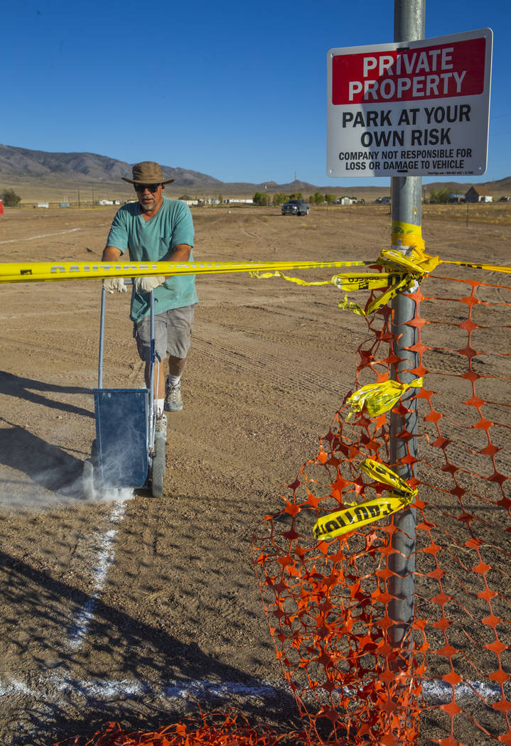 Douglas Benedetti chalks out parking lines across from the Little A'Le'Inn which is the site of ...