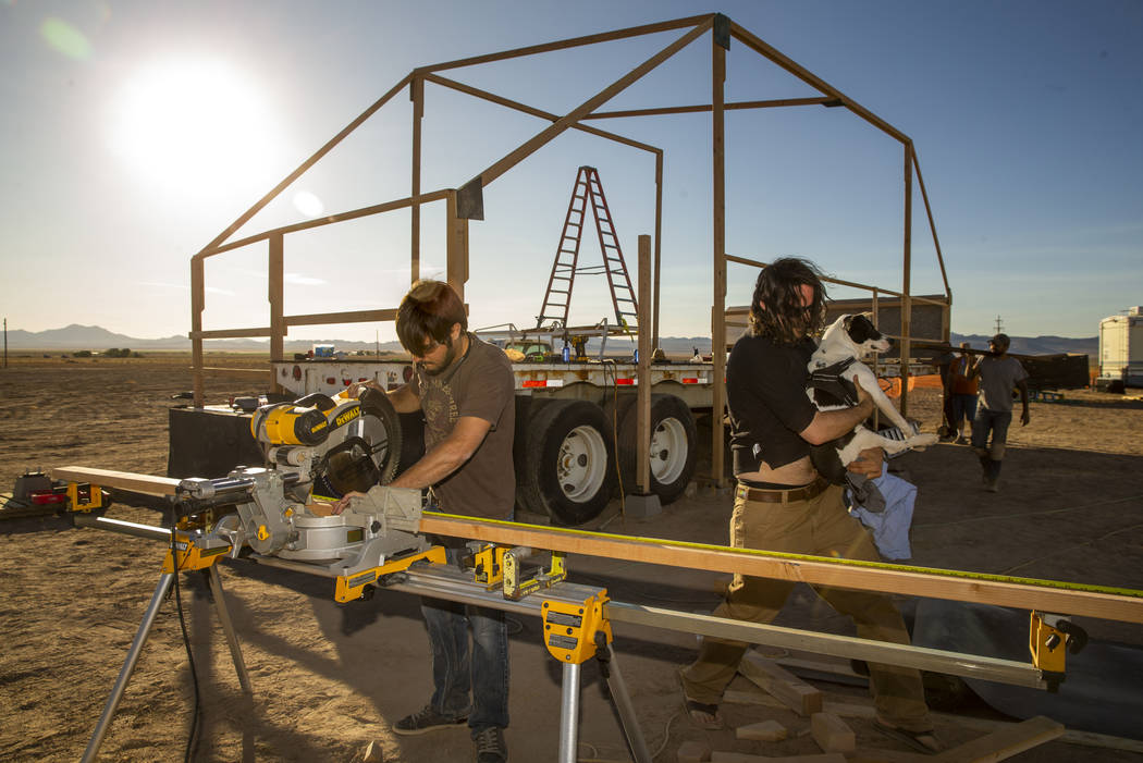 Jesse Morrow, left, works with others to construct the main stage for the upcoming Alienstock f ...