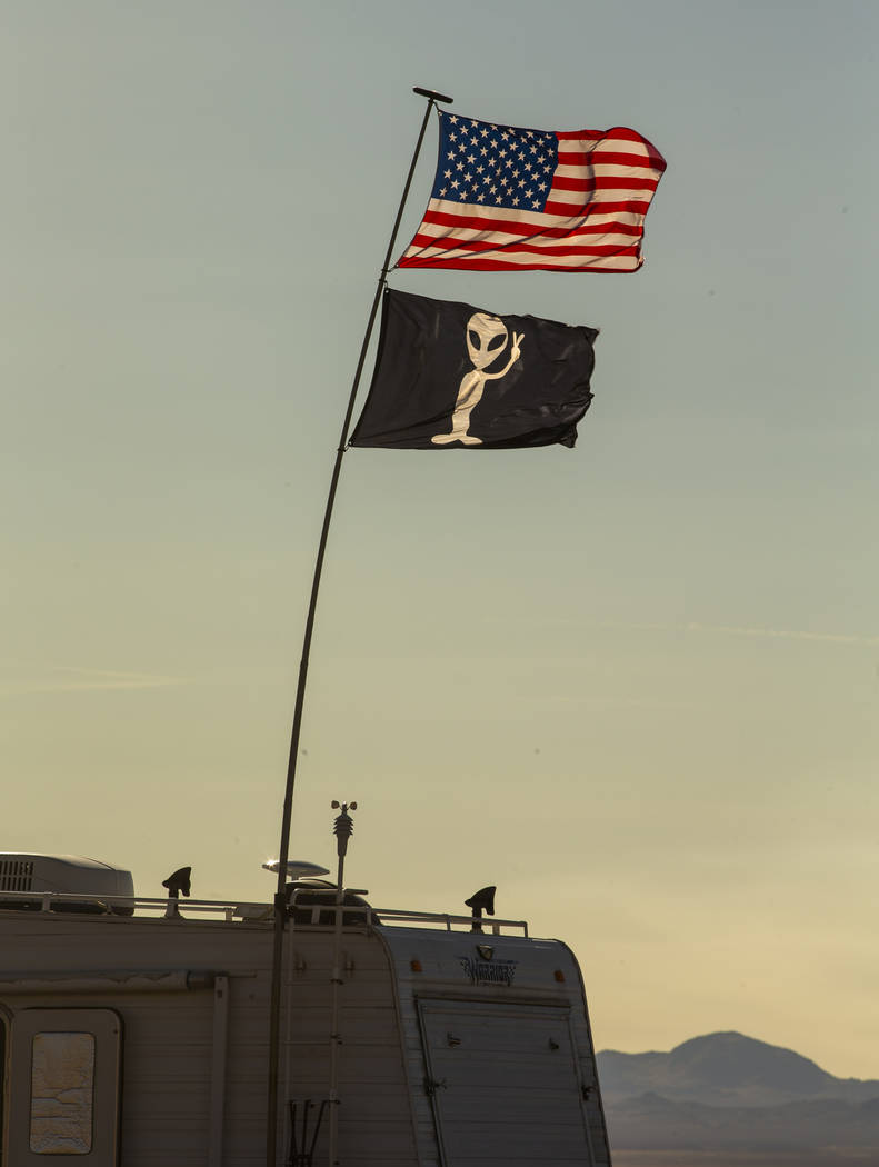 Two flags fly above and RV which is camped out in the desert as the Alienstock and Area 51 Base ...