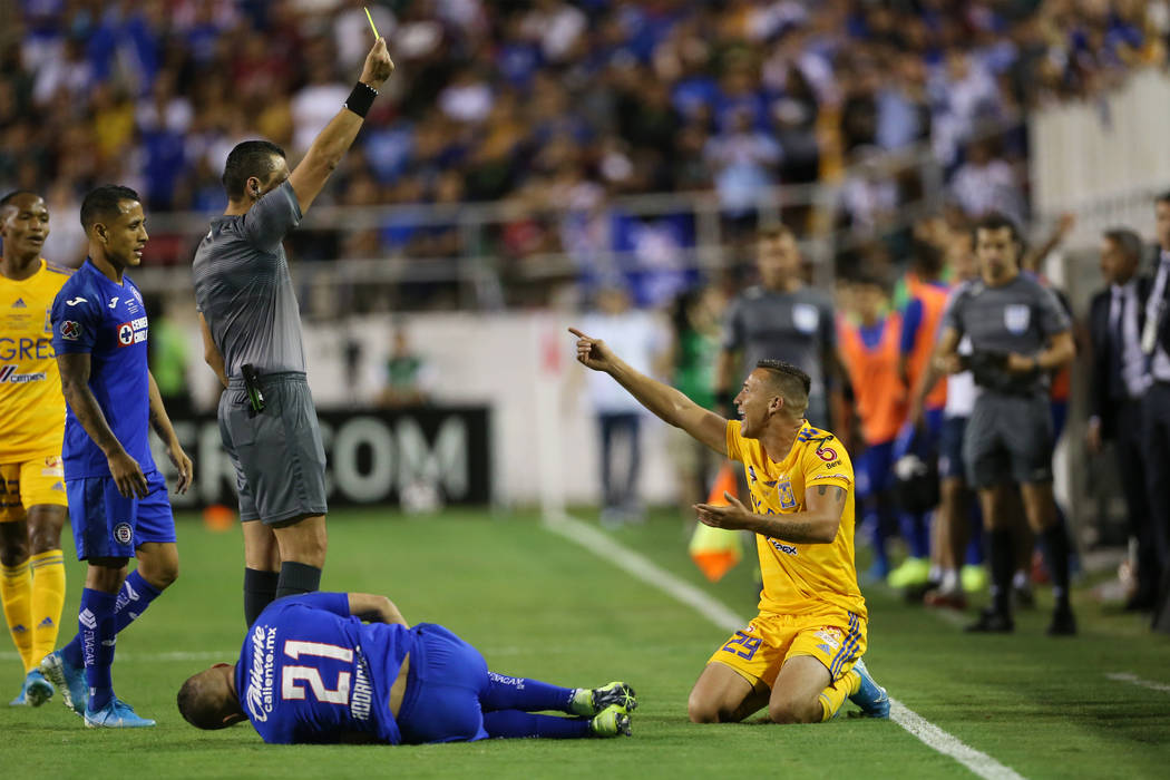 Tigres' Jesus Duenas (29), right, receives a yellow card for a foul against Cruz Azul's Jonatha ...