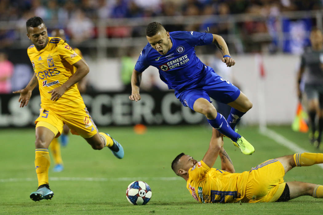 Tigres' Rafael Carioca (5), left, watches his teammate Jesus Duenas (29) slide against Cruz Azu ...