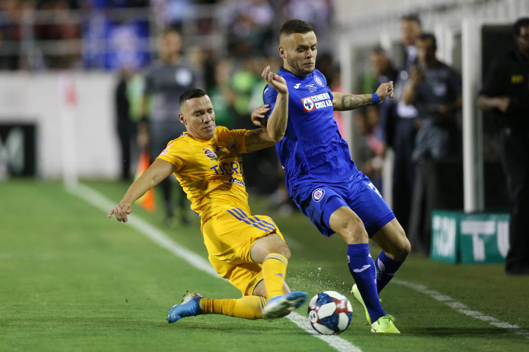 Tigres' Jesus Duenas (29), left, fight for the ball against Cruz Azul's Jonathan Rodriguez (21) ...