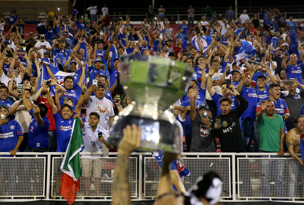 Fans celebrate with Cruz Azul's Edgar Mendez (17) holding the trophy after defeating Tigres 2-1 ...