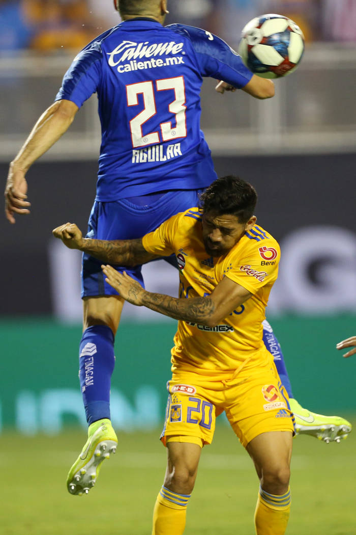 Tigres' Javier Aquino (20) and Cruz Azul's Pablo Aguilar (23) leap for the ball during the seco ...