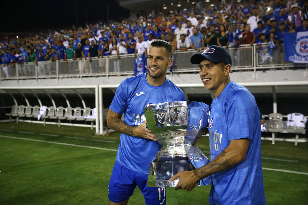 Cruz Azul's Edgar Mendez (17), left, and Julio Dominguez (4), hold the trophy after their team ...
