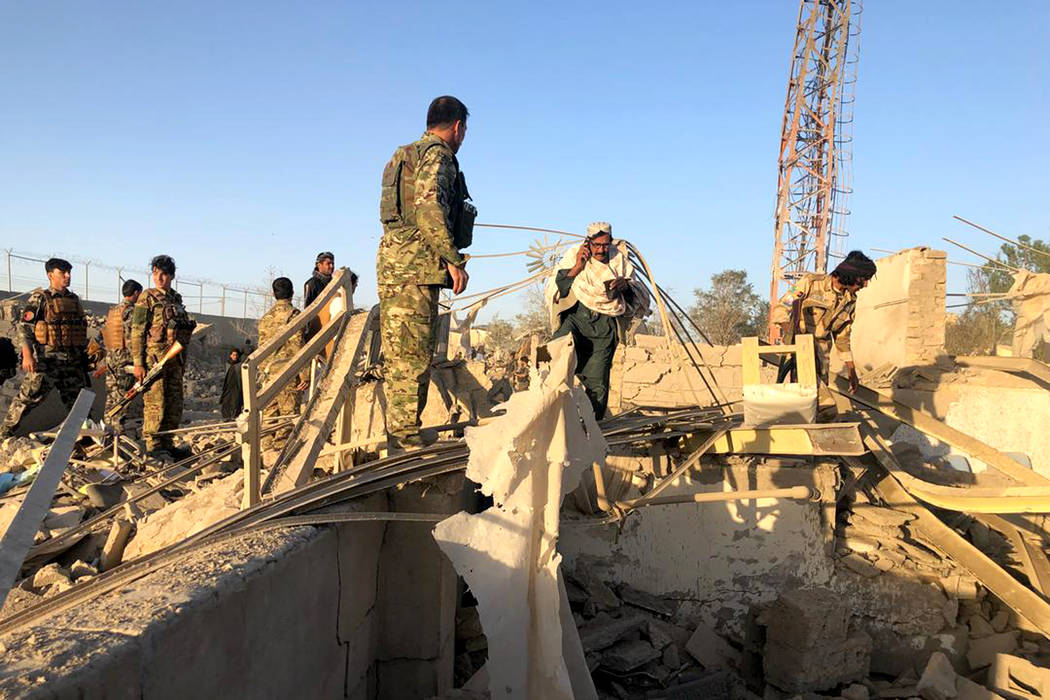 Afghan security members and people work at the site of a suicide attack in Zabul, Afghanistan, ...