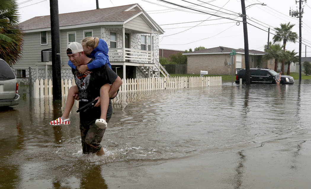 Terry Spencer carries his daughter, Trinity, through high water on 59th Street near Stewart Roa ...