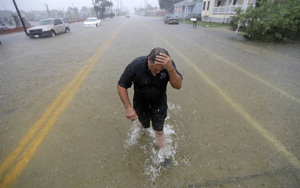 Angel Marshman wades through floodwaters from Tropical Depression Imelda after trying to start ...