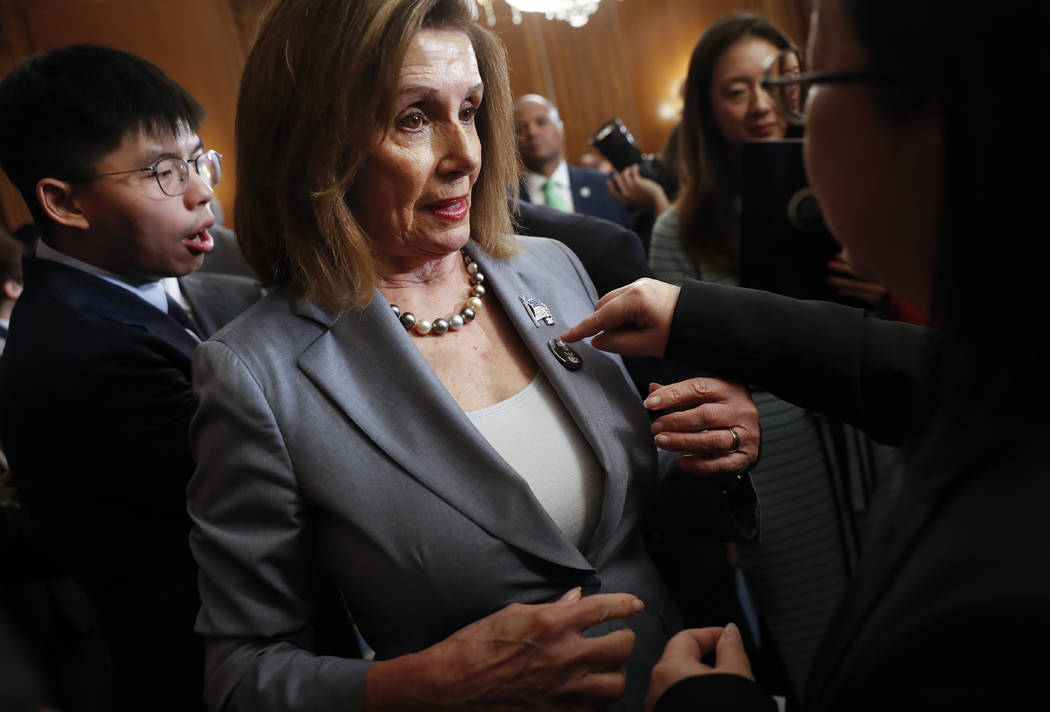 House Speaker Nancy Pelosi is given a lapel pin by a Hong Kong activist following a news confer ...
