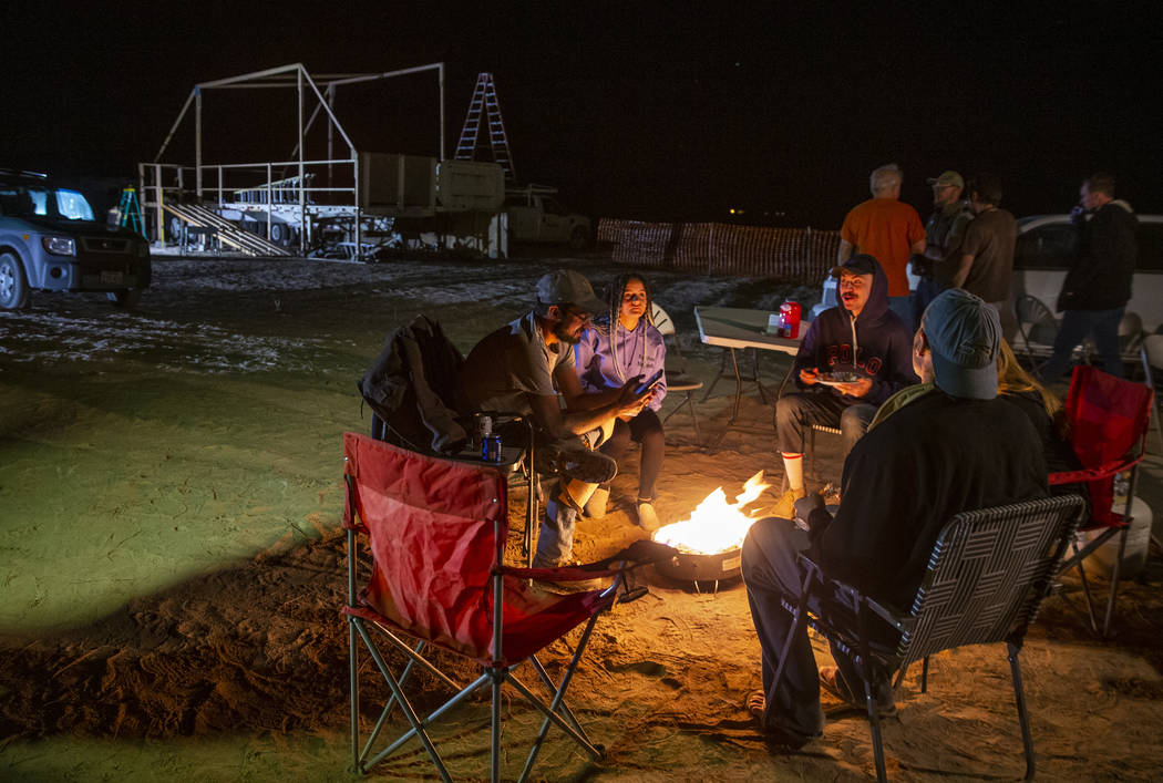 Friends hang out and warm up by a gas fire pit near the main stage still under construction as ...