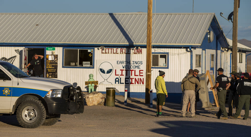 Samantha Travis, left, peers out the door of the Little A'Le'Inn as law enforcement officers wa ...