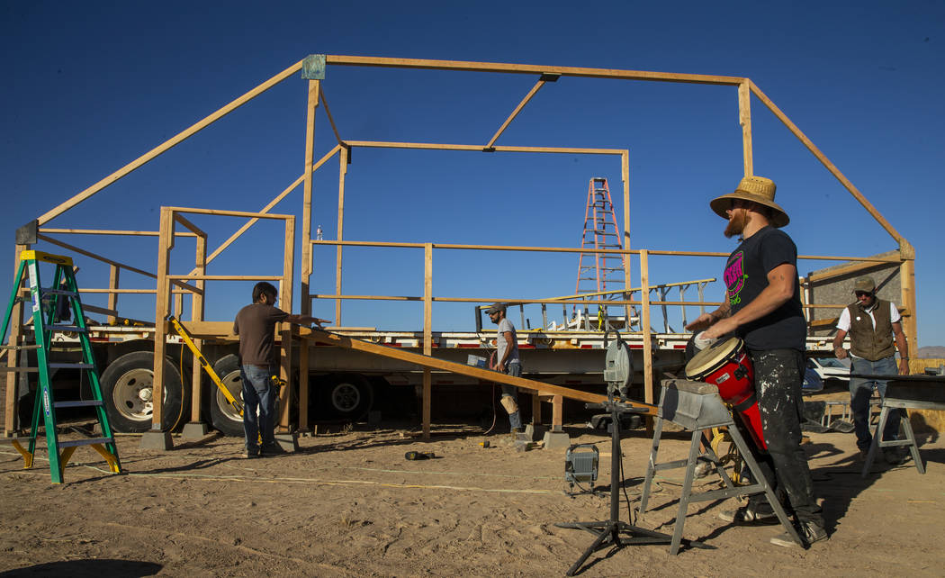 Wily Savage lead singer Alon Burton plays a conga drum as the construction crew begins work on ...