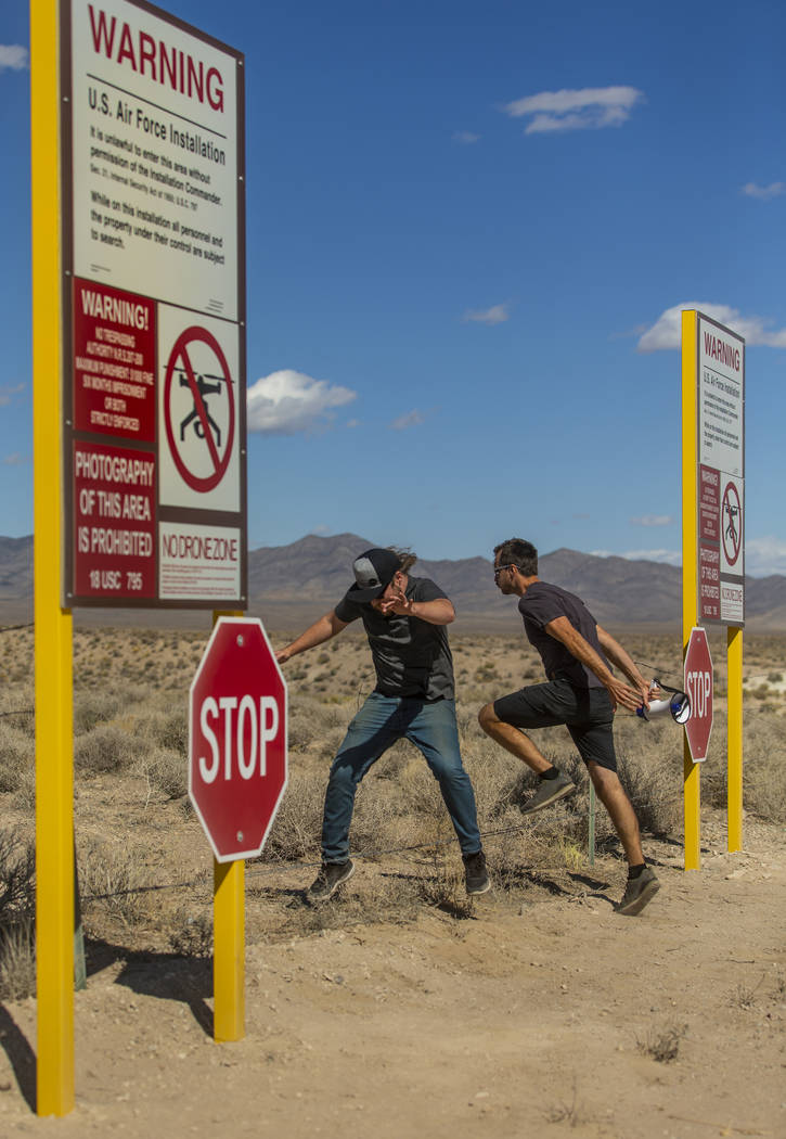 Devin Caldarone, left, and Mike Dye of Los Angeles pretend to cross into Area 51 past the fake ...