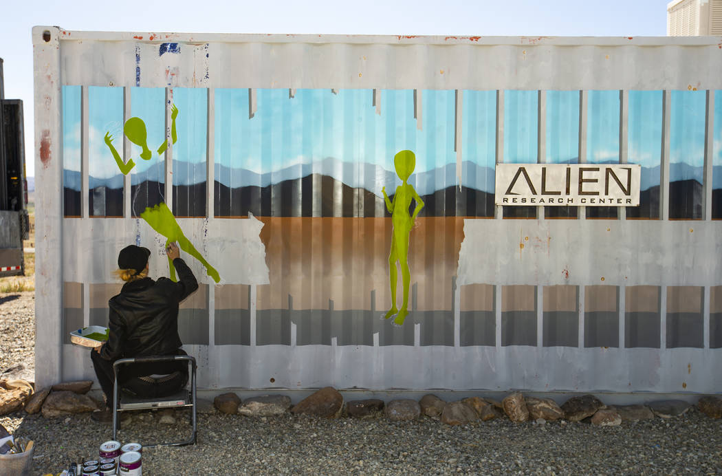 Artist Brandy Whisenant paints a mural on the side of a container at the Area 51 Basecamp at th ...