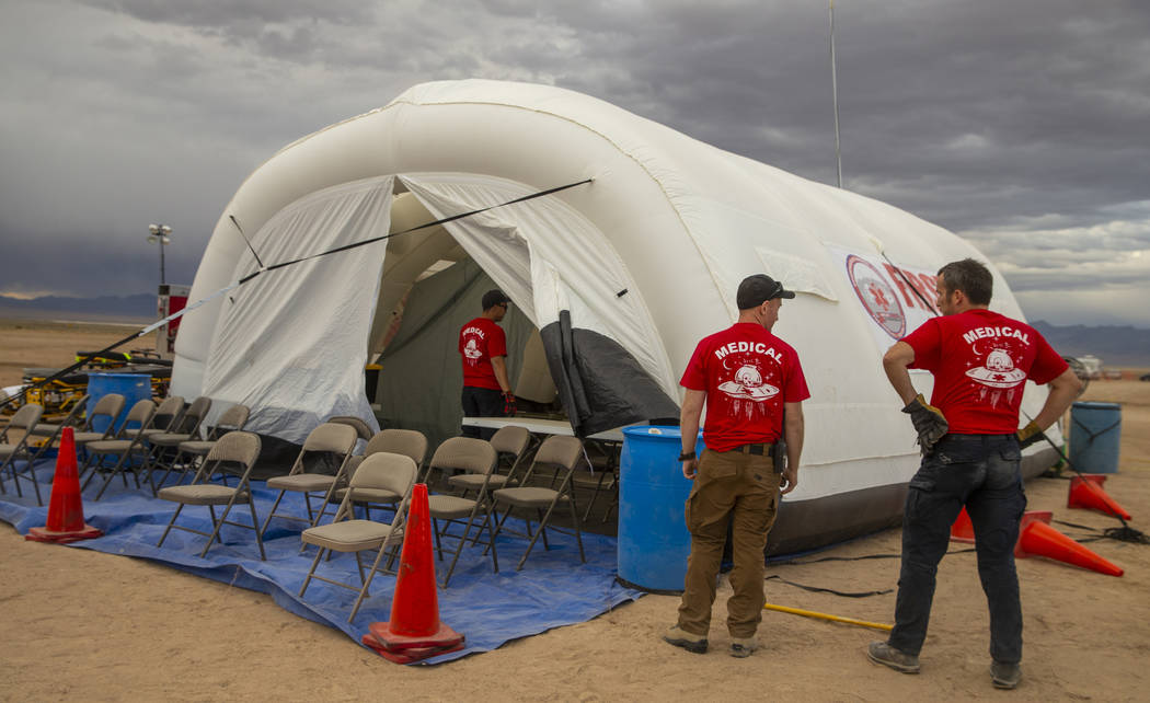The medical crew looks to tamp down their tent while winds pick up as the start of the Aliensto ...