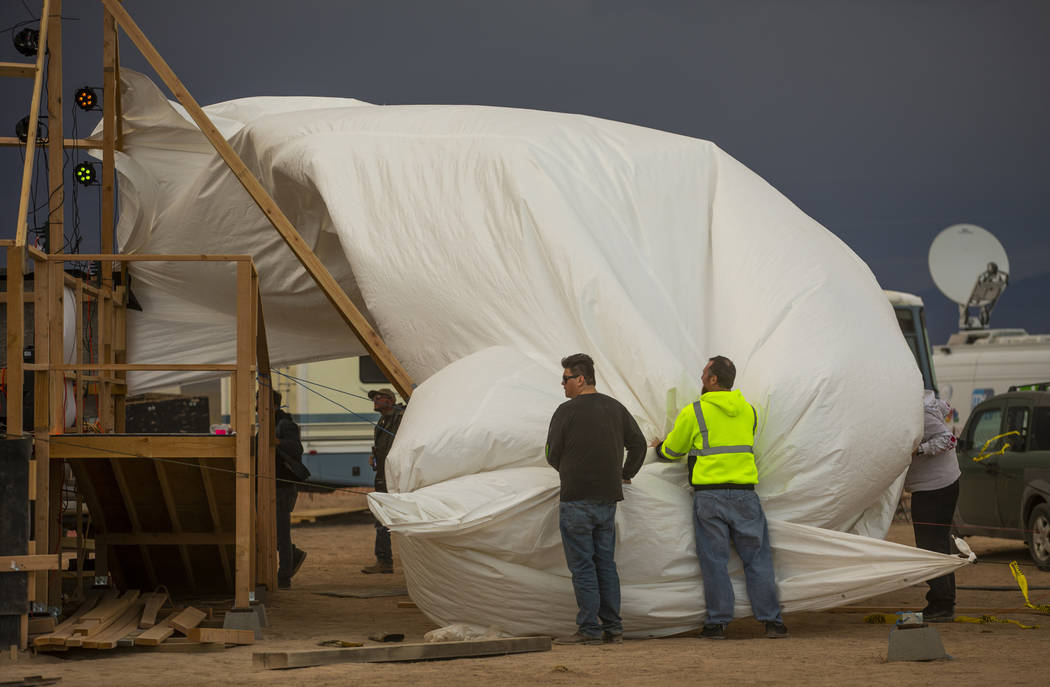 Volunteers help to secure the roof tarp on the main stage while it blows off from increasing wi ...