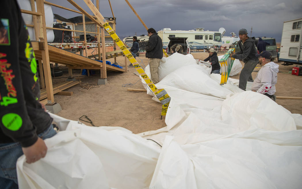 Volunteers help to secure the roof tarp from the main stage after it blows off from increasing ...