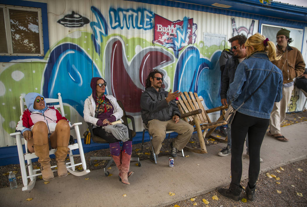 Festivalgoers get some break from the high winds by hanging out in front of the Little'A'Le'Inn ...