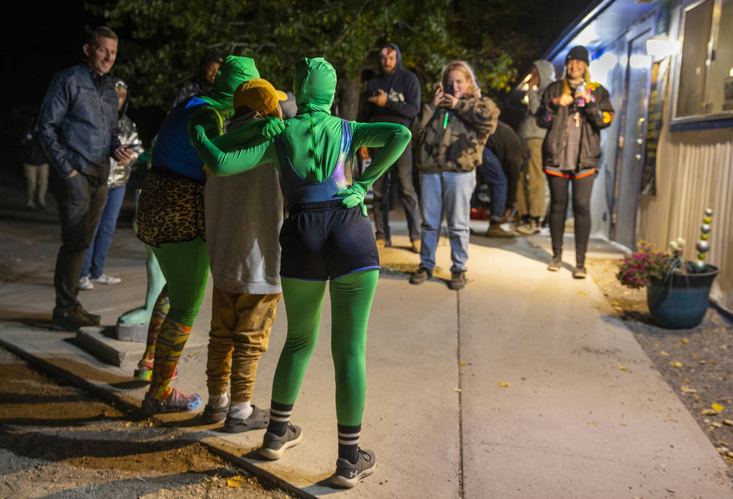 Festivalgoers hang out with some aliens at the Little A'Le'Inn late on the first night of Alien ...