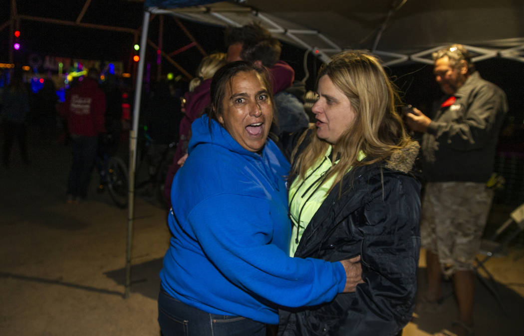 Connie West of the Little A'Le'Inn, left, hugs a festivalgoer asWill Shamberger and Wily ...