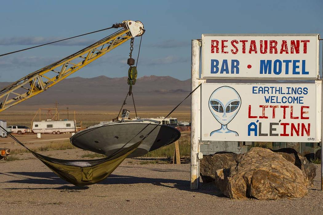 A camper sleeps in a hammock on the sign outside the Little A'Le'Inn which will serve coffee an ...