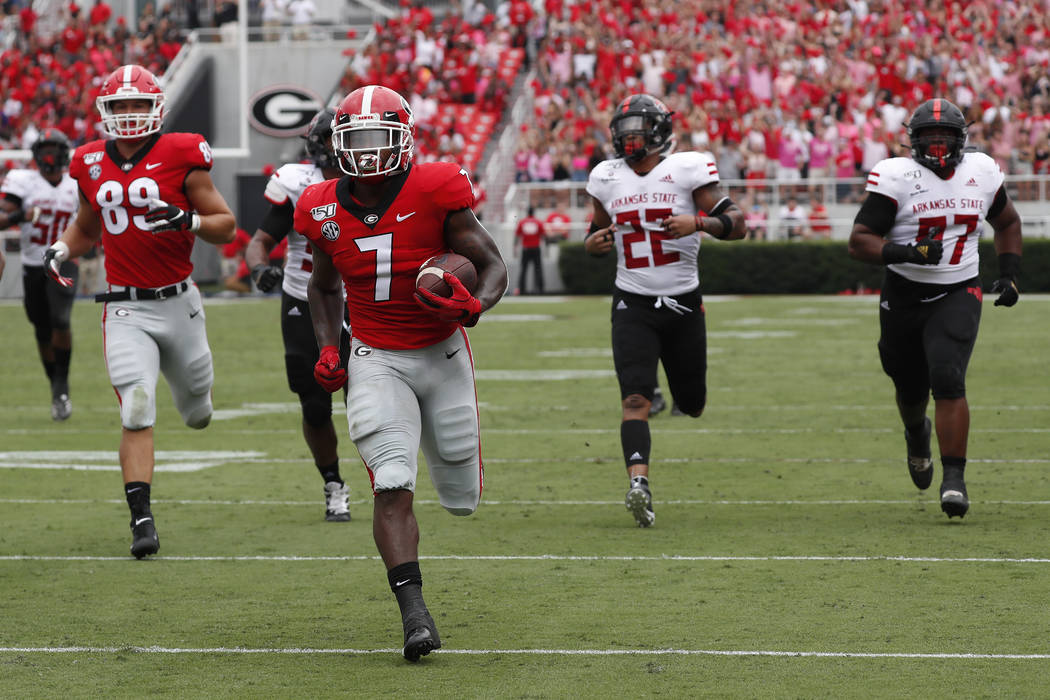 Georgia running back D'Andre Swift (7) is chased by the Arkansas State defense as he scores a t ...
