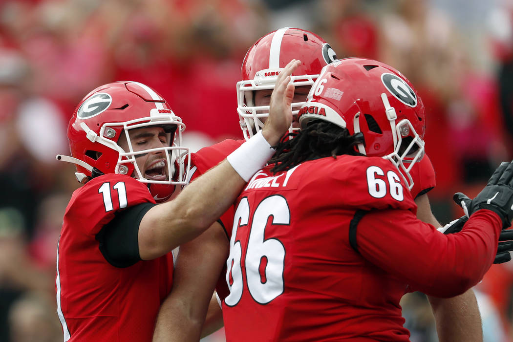 Georgia quarterback Jake Fromm (11) celebrates with offensive lineman Solomon Kindley (66) afte ...