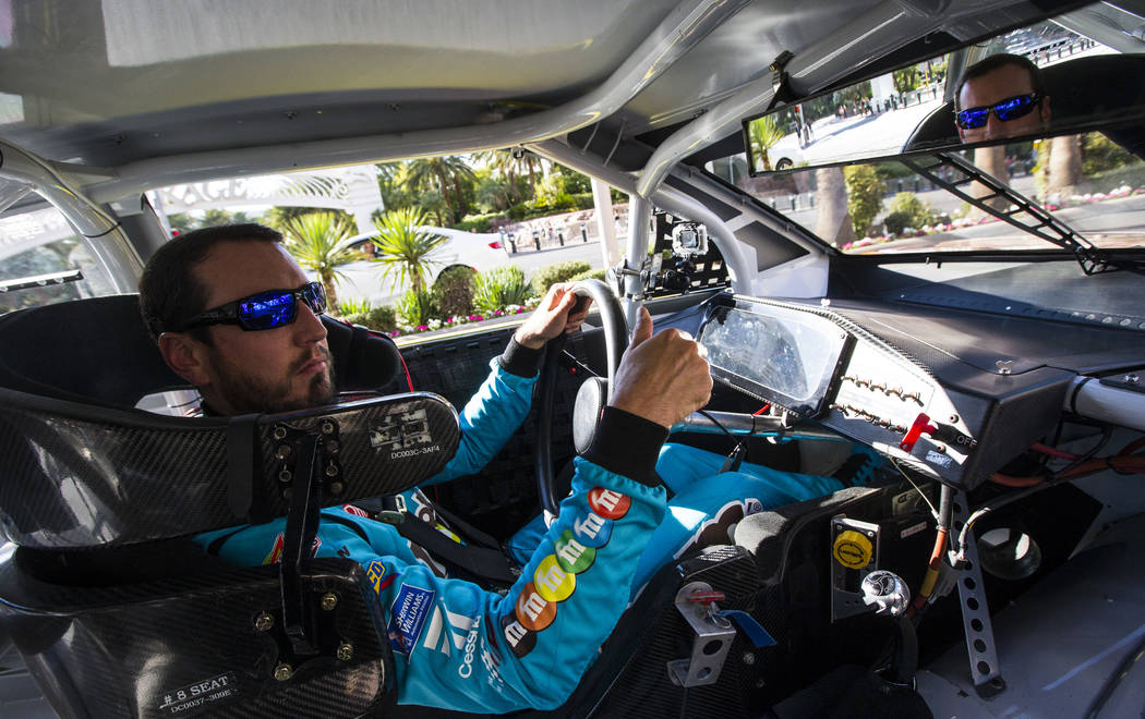 Kyle Busch motions to fans while passing The Mirage and The Venetian while driving down the Las ...