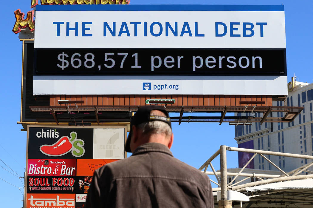 A pedestrian walks past a billboard depicting rising national debt on Las Vegas Boulevard direc ...