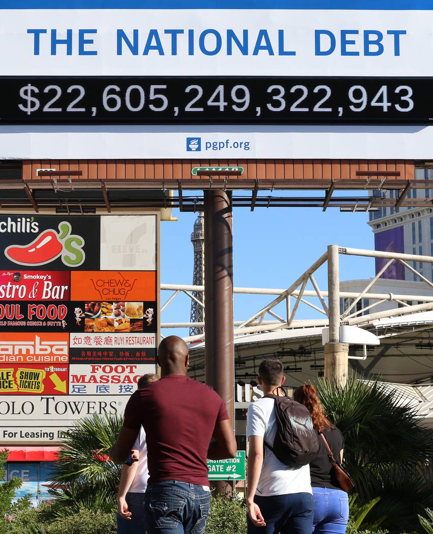 Pedestrians walk past a billboard depicting rising national debt on Las Vegas Boulevard directl ...